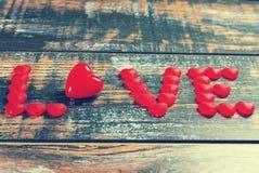 La parola AMORE fatto delle caramelle e del cuore rossi Immagine Stock