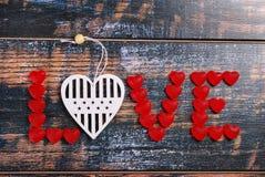 La parola AMORE fatto delle caramelle rosse e del cuore bianco Fotografia Stock