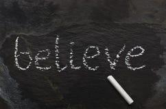 La parola BELIEVE scritto con gesso sulla pietra nera Fotografia Stock Libera da Diritti