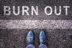 La parola brucia scritto su asfalto con le gambe e le scarpe Fotografia Stock Libera da Diritti