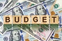 La parola, Butget ha composto di lettere sulle particelle elementari di legno contro lo sfondo delle banconote in dollari Affare  Fotografie Stock Libere da Diritti