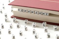 La parola che capisce la vittoria scritta lettere cirilliche fra gli strati del libro e le lettere cirilliche sparge sul sommario fotografia stock