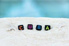La parola Cuba è fatta delle lettere multicolori sulla sabbia bianca come la neve contro il mare blu Fotografia Stock Libera da Diritti