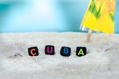 La parola Cuba è fatta delle lettere multicolori sulla sabbia bianca come la neve contro il mare blu Fotografie Stock