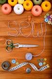 La parola cuce con gli strumenti e gli accessori di cucito su fondo di legno Immagini Stock