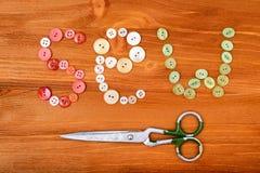 La parola cuce dai bottoni di cucito multicolori e dalle forbici su fondo di legno Fotografia Stock