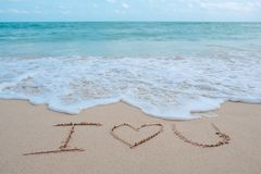 La parola di scrittura della mano ti amo sulla spiaggia dal mare con le onde ed il cielo blu di bianco Fotografie Stock