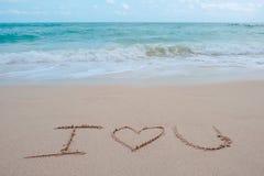 La parola di scrittura della mano ti amo sulla spiaggia dal mare con le onde ed il cielo blu di bianco Fotografia Stock