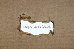 La parola fa riferimento un amico che compare dietro la carta lacerata immagine stock