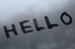 La parola inglese ciao è scritta con un dito sulla superficie del vetro appannato fotografia stock