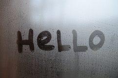 La parola inglese ciao è scritta con un dito sulla superficie del vetro appannato fotografia stock libera da diritti