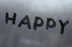 La parola inglese felice è scritta con un dito sulla superficie del vetro appannato immagine stock