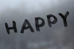 La parola inglese felice è scritta con un dito sulla superficie del vetro appannato fotografia stock