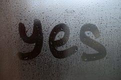 La parola inglese sì è scritta con un dito sulla superficie del vetro appannato immagini stock