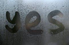 La parola inglese sì è scritta con un dito sulla superficie del vetro appannato fotografia stock libera da diritti