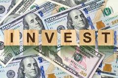 La parola, Invest ha composto di lettere sulle particelle elementari di legno contro lo sfondo delle banconote in dollari Affare  Immagini Stock Libere da Diritti