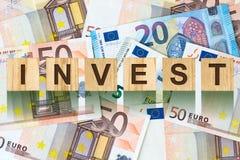La parola, Invest ha composto di lettere sulle particelle elementari di legno contro lo sfondo di euro banconote Affare di concet Immagini Stock Libere da Diritti