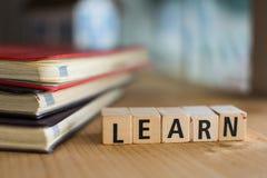 La parola LEARN ha compitato con i blocchetti di legno variopinti dell'alfabeto Fotografie Stock