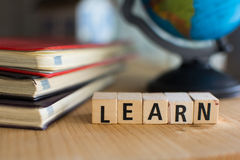 La parola LEARN ha compitato con i blocchetti di legno variopinti dell'alfabeto Fotografia Stock