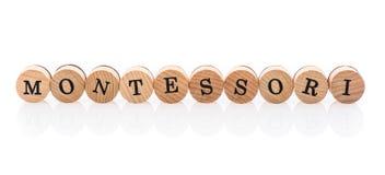 La parola Montessori dalle mattonelle di legno circolari con i bambini delle lettere gioca immagini stock libere da diritti