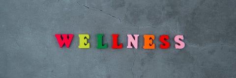 La parola multicolore di benessere è fatta delle lettere di legno su un fondo intonacato grigio della parete fotografie stock libere da diritti