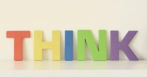 La parola PENSA, nelle lettere maiuscole variopinte dei giocattoli della schiuma Fotografia Stock