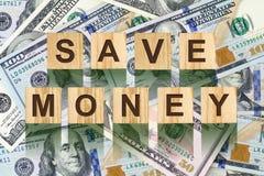 La parola, risparmia i soldi composti di lettere sulle particelle elementari di legno contro lo sfondo delle banconote in dollari Fotografia Stock