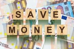 La parola, risparmia i soldi composti di lettere sulle particelle elementari di legno contro lo sfondo di euro banconote Affare d Immagine Stock Libera da Diritti