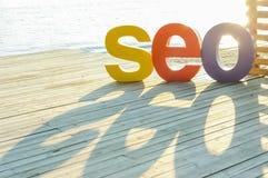 La parola SEO dalle grandi lettere colorate che creano un'ombra sul terrazzo di legno sulla sponda del fiume Lampadina di Sun Fuo Immagini Stock
