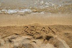 La parola SI RILASSA in sabbia Immagini Stock