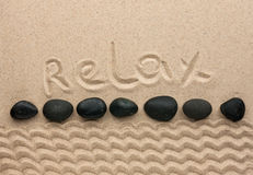 La parola si rilassa scritto sulla sabbia Fotografia Stock Libera da Diritti