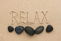 La parola si rilassa scritto sulla sabbia Immagini Stock Libere da Diritti