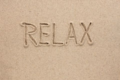 La parola si rilassa scritto sulla sabbia Fotografie Stock