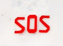 La parola SOS su un campo di neve Fotografie Stock