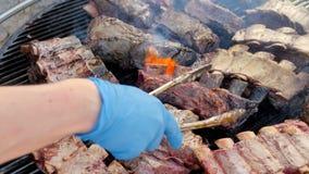 La parrilla americana, cocinero da vuelta a la carne en la parrilla con las llamas del fuego Freír costillas de cerdo de la barba almacen de video