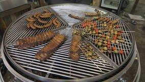 La parrilla redonda grande se divide en los segmentos, que tiene un diferente tipo de carne y de verduras, la parrilla almacen de metraje de vídeo