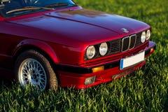 La parte anteriore di vecchia, automobile rossa e tedesca che sta sull'erba fotografia stock