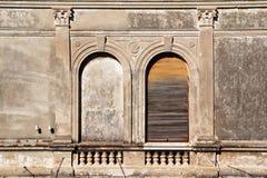 La parte de edificio residencial con los obturadores y la ventana de madera de las ventanas viejas se empareda para arriba, prime Fotos de archivo libres de regalías