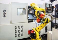 La parte della fresatrice di CNC con il pannello di controllo e del robot nel mosso muove una parte dal CNC sul trasportatore immagine stock