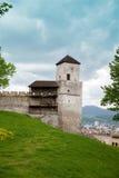 La parte della parete del castello con l'orologio di torretta in Trencin Fotografie Stock