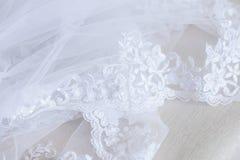 La parte di un velo bianco di Tulle di nozze con il ricamo dei fiori che mette su una superficie beige, aspetta per la futura spo Fotografia Stock