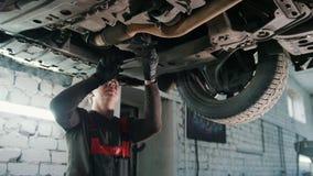 La parte inferior del mecánico automotriz del trabajador comprueba - servicio del automóvil metrajes