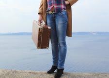 La parte inferiore di girl's calcola con la vecchia valigia marrone sulla spiaggia Fotografie Stock