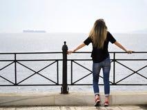 La parte posterior de la muchacha delante del mar foto de archivo libre de regalías