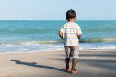 La parte posterior de la situación del niño pequeño corre en la playa Foto de archivo