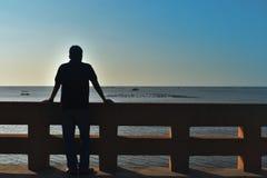 La parte posterior de la sombra del hombre de Asia 40 años el frente es el mar Imagen de archivo libre de regalías
