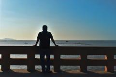 La parte posterior de la sombra del hombre de Asia 40 años el frente es el mar foto de archivo