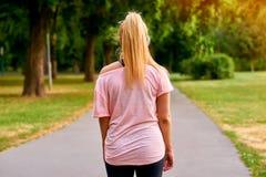 La parte posterior de una mujer corriente en un parque Imagen de archivo libre de regalías