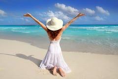 La parte posterior del Caribe de la mujer de la playa en rodillas abre los brazos fotografía de archivo libre de regalías