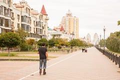 La parte posterior del patinador del rodillo monta por la acera en ciudad imagen de archivo libre de regalías